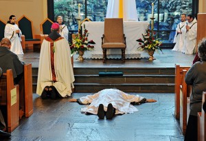 Friar Gabriel Mary Scasino lies prostrate as a sign of humility as the congregation invokes the intercession of the communion of saints in the singing of the Litany of Saints. Photo By Lee Depkin
